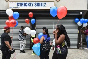 Mourners pay tribute to Zanu Simpson at Strickly Skillz Barber shop in Hollis, Queens